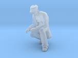 Man Kneeling: Long Coat & Cap