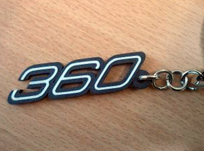 Keychain 360 logo in Black Matte Steel with white plastic inserts.