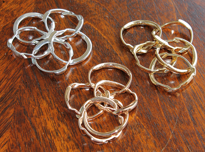 WOW5 Puzzle Ring 3d printed Interlocking Silver, Bronze, and Brass in the scrambled state.