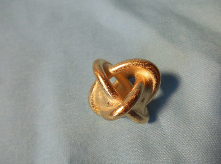 Unusual twisted D8 (rings) 3d printed This is a picture of the 40mm variant in polished gold steel.