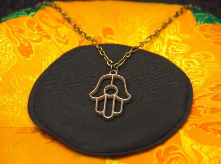 Hamsa Pendant 3d printed Photo of Stainless Steel pendant on a chain.