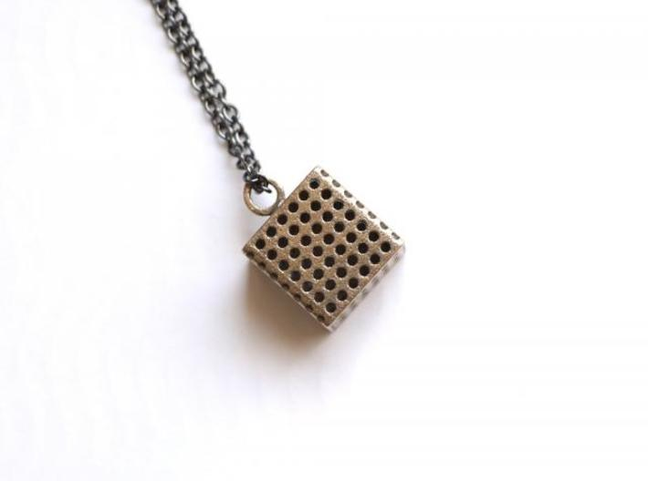 Perforated Cube Pendant  3d printed steel cube against white background