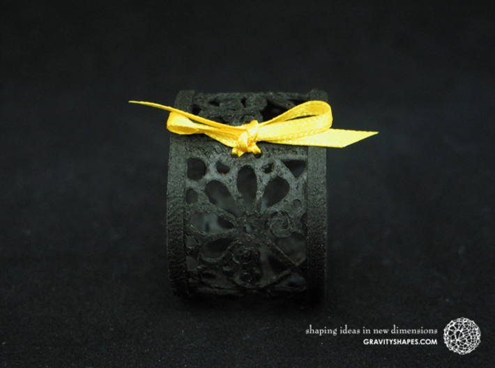 A small napkin ring with Mosaic-3b 3d printed The photo shows an own print (FDM print) made of black wood incl. decorative lacing.