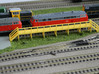 N Scale Train Maintenance Platform DOUBLE STAIRS 3d printed Train maintenance platform with two stairs in Yellow Strong & Flexible Polished, unpainted. The base is covered in grass.